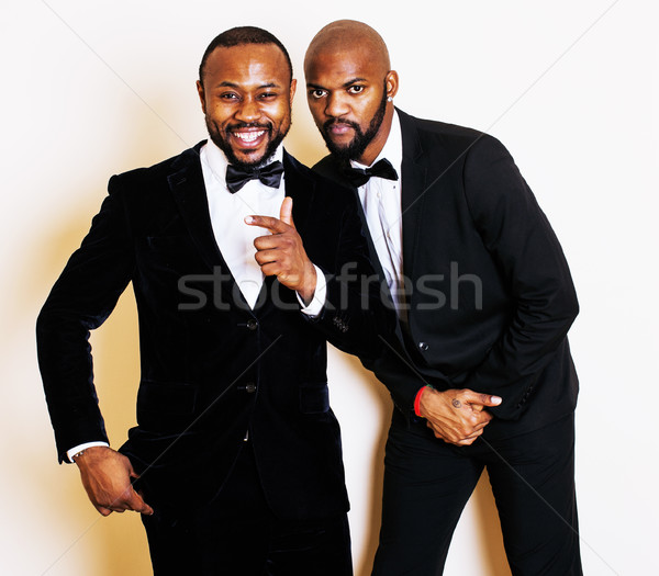 two afro-american businessmen in black suits emotional posing, gesturing, smiling. wearing bow-ties  Stock photo © iordani
