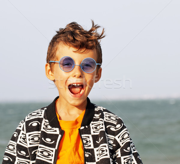 cute little boy at seacoast in fashion clothers and blue glasses Stock photo © iordani