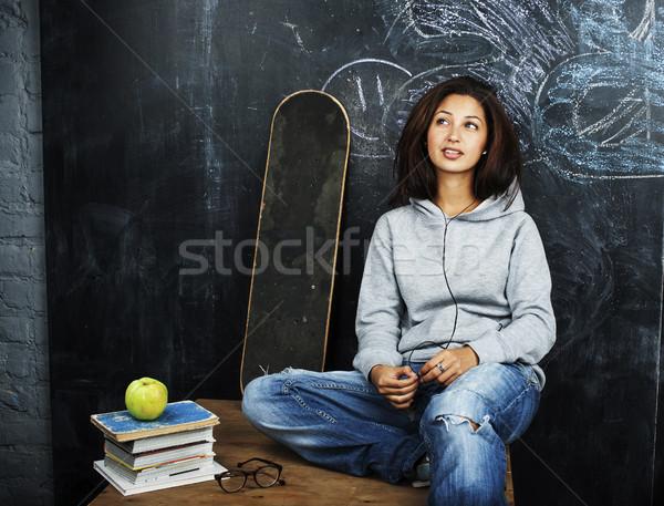 young cute teenage girl in classroom at blackboard seating on ta Stock photo © iordani