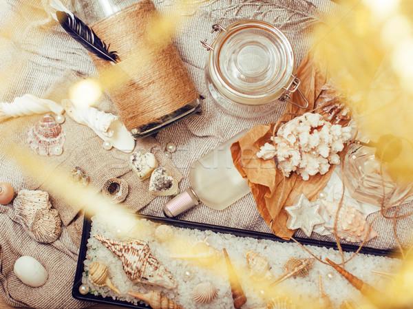 a lot of sea theme in mess like shells, candles, perfume, girl stuff on linen, pretty textured post  Stock photo © iordani