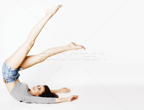 young pretty brunette woman head over heels on white isolated Stock photo © iordani