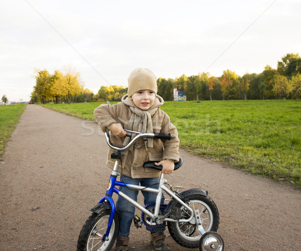 little cute real boy on bicycle emotional smiling close up outside in green amusement park Stock photo © iordani