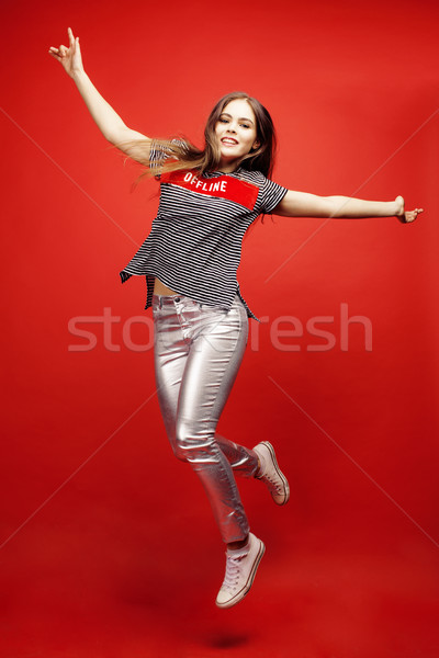 young pretty emitonal posing teenage girl on bright red background jumping with flying hair, happy s Stock photo © iordani
