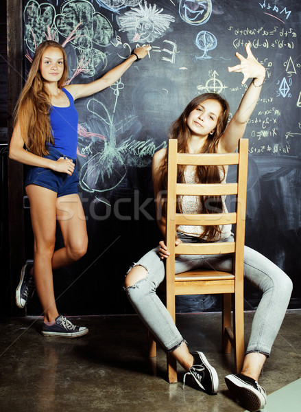 back to school after summer vacations, two teen girls in classroom with blackboard painted together Stock photo © iordani
