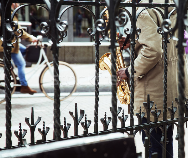 african street musician playing jazz on saxophone throw lattice  Stock photo © iordani