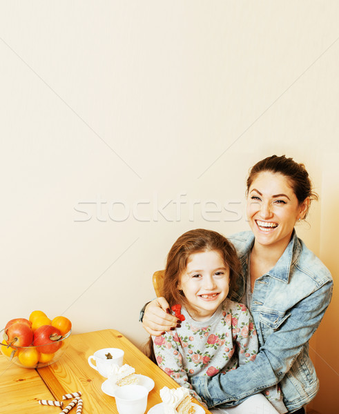 young mother with daughter on kitchen drinking tea together hugging eating celebration cake on birth Stock photo © iordani