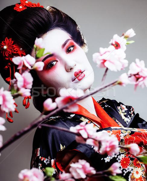 Stock photo: young pretty geisha in kimono with sakura and red decoration des