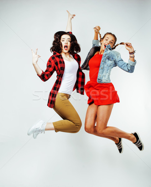 two pretty brunette and blonde teenage girl friends jumping happy smiling on white background, lifes Stock photo © iordani