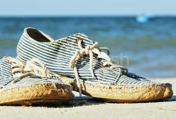 Stock photo: picture of vintage old shabby sneakers at seacost, real forgotte