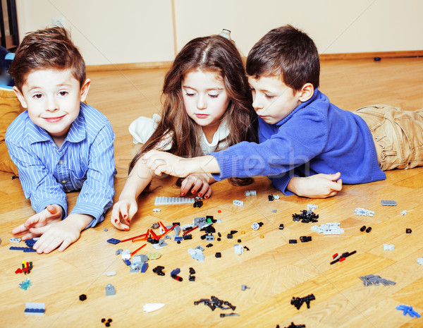 funny cute children playing lego at home, boys and girl smiling, first education role lifestyle Stock photo © iordani