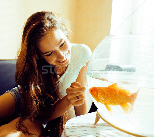 Hübsche Frau spielen Goldfisch home Sonnenlicht Morgen Stock foto © iordani