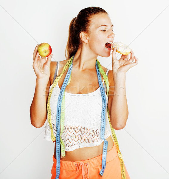 young blonde woman choosing between donut and apple fruit isolated on white background, lifestyle pe Stock photo © iordani