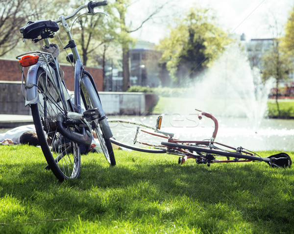 lifestyle people concept: couple of bicycle on green grass in summer park at fountain Stock photo © iordani