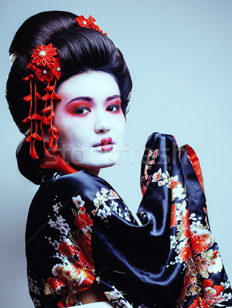 young pretty geisha in kimono with sakura and red decoration des Stock photo © iordani