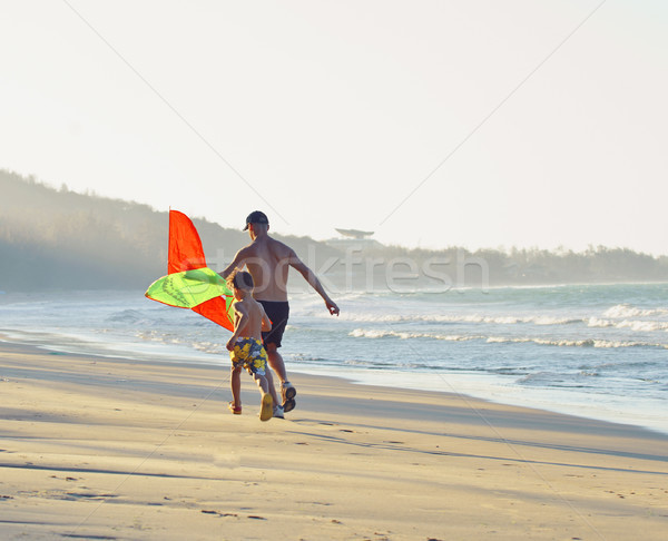 Stock photo: father with son, sunset at the seacoast with kite, happy family