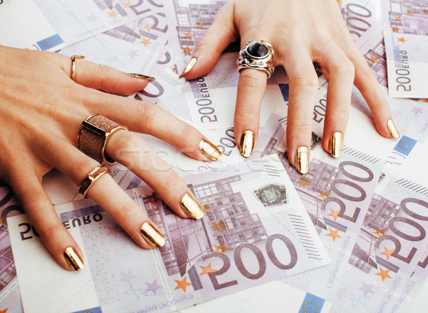 hands of rich woman with golden manicure and many jewelry rings  Stock photo © iordani