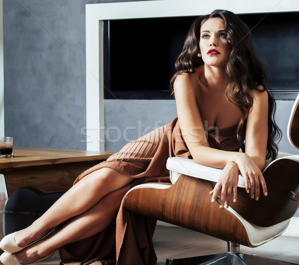 beauty yong brunette woman sitting near fireplace at home, winter warm evening in interior, waiting  Stock photo © iordani