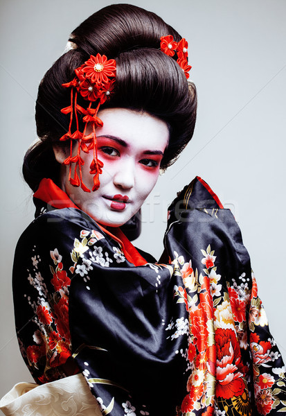 young pretty geisha in kimono with sakura and red decoration design on white background Stock photo © iordani