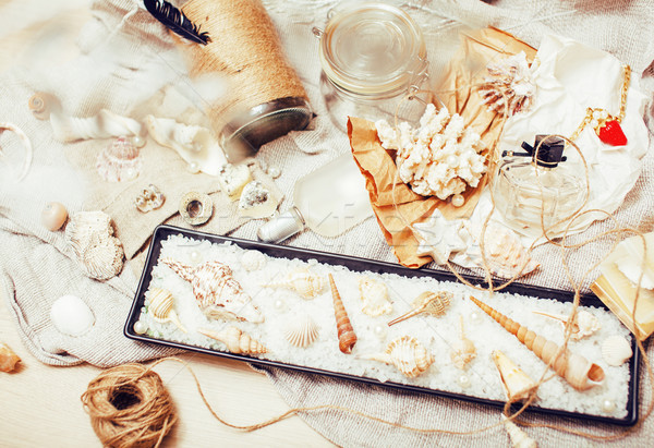 a lot of sea theme in mess like shells, candles, perfume, girl s Stock photo © iordani