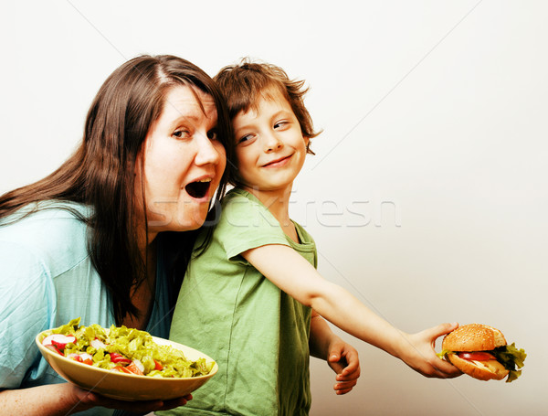 fat woman holding salad and little cute boy with hamburger on white background Stock photo © iordani