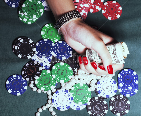 hands of young caucasian woman with red manicure at casino table close up Stock photo © iordani