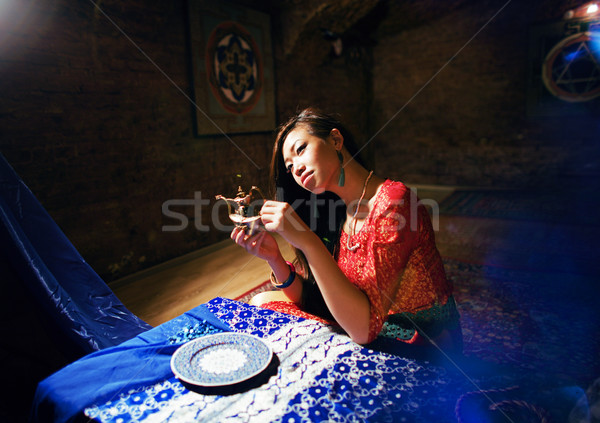 young pretty asian girl in bright colored interior on carpet vie Stock photo © iordani