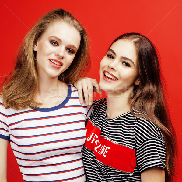 two best friends teenage girls together having fun, posing emotional on red background, besties happ Stock photo © iordani