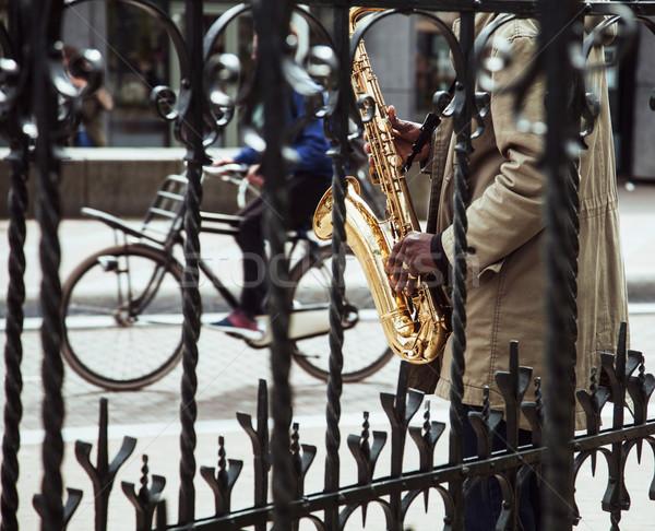 african street musician playing jazz on saxophone throw lattice  Stock photo © iordani