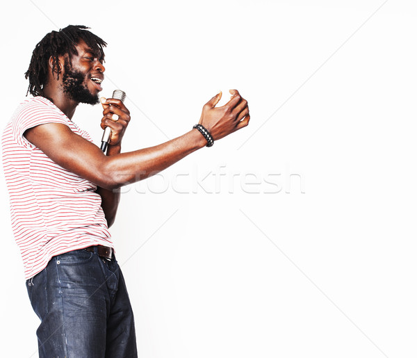 young handsome african american boy singing emotional with microphone isolated on white background,  Stock photo © iordani