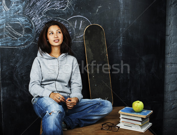 young cute teenage girl in classroom at blackboard seating on table smiling, modern hipster concept, Stock photo © iordani