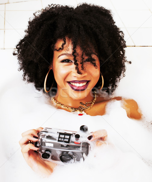 young afro-american teen girl laying in bath with foam, wearing  Stock photo © iordani