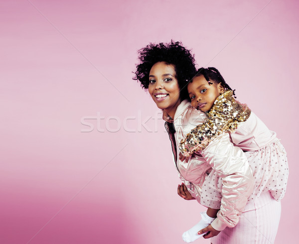 young pretty african-american mother with little cute daughter hugging, happy smiling on pink backgr Stock photo © iordani