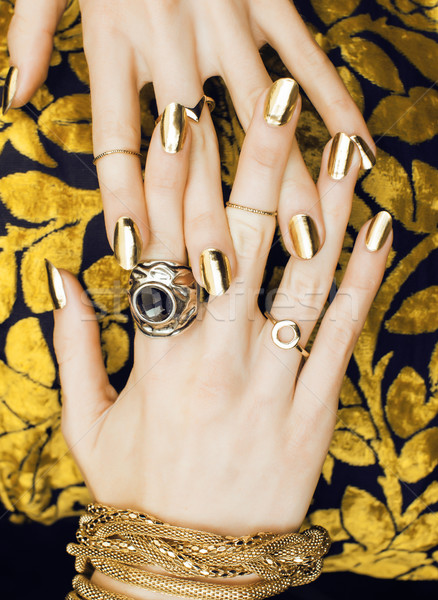 woman hands with golden manicure lot of jewelry on fancy dress close up Stock photo © iordani