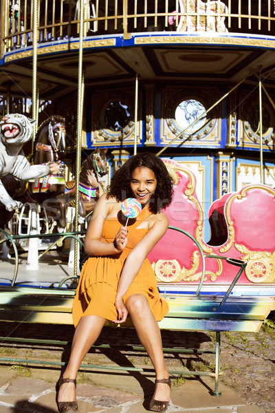 cool real teenage girl with candy near carousels at amusement pa Stock photo © iordani