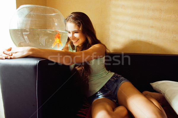 pretty woman playing with goldfish at home, sunlight morning Stock photo © iordani