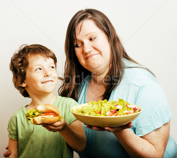 fat woman holding salad and little cute boy with hamburger teasing Stock photo © iordani