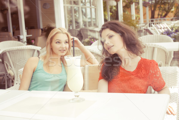 portrait of two pretty modern girl friends in cafe open air interior drinking and talking, having ch Stock photo © iordani