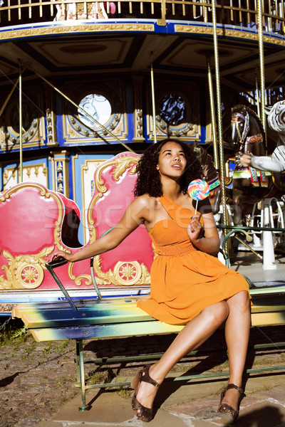 cool real african american teenage girl with candy near carousels at amusement park, lifestyle peopl Stock photo © iordani