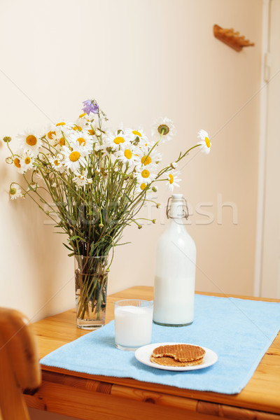 Simply stylish wooden kitchen with bottle of milk and glass on table, summer flowers camomile, healt Stock photo © iordani