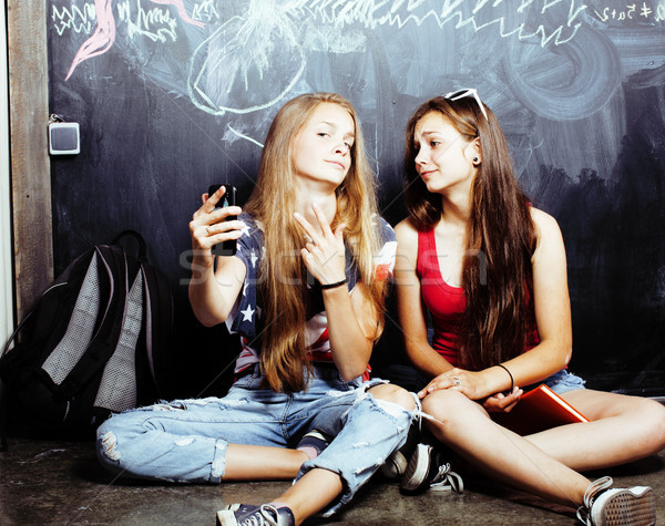 Stock photo: back to school after summer vacations, two teen real girls in classroom with blackboard painted toge