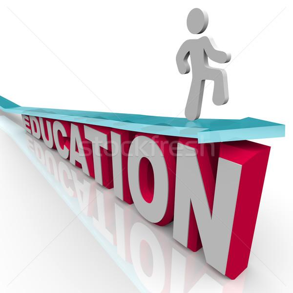 Education - Man Rides Arrow Over Word Stock photo © iqoncept