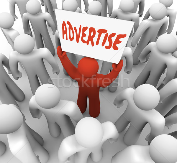 Advertise Man Holds Banner Sign to Attract Customers in Crowd Stock photo © iqoncept