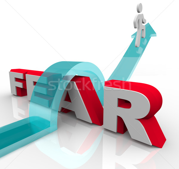 Stock photo: Conquering Your Fears - Jumping Over Word to Beat Fear