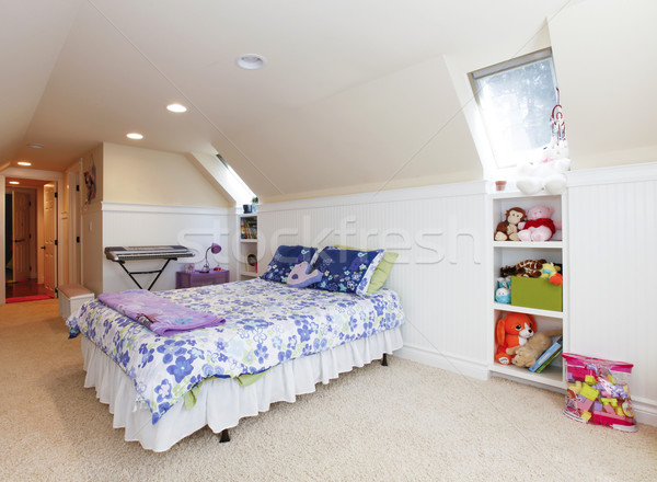 Girl bedroom with attic ceiling and beige carpet with toys. Stock photo © iriana88w