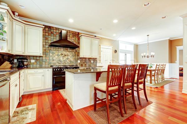 Luxury white kitchen with cherry hardwood and island with chairs. Stock photo © iriana88w