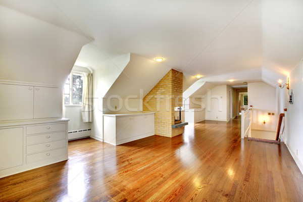 Large long attic room with fireplace. Empty with golden hardwood. Stock photo © iriana88w