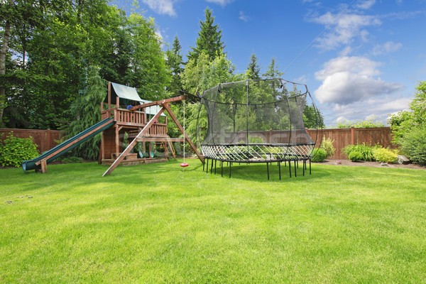 Play kinds ground area with tremplin in fenced backyard. Stock photo © iriana88w