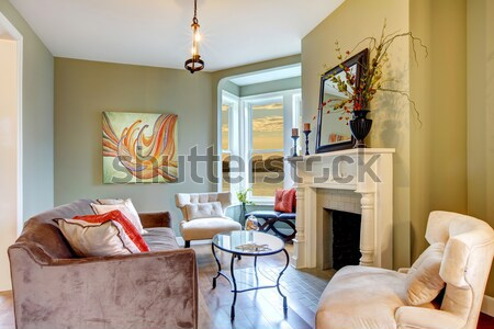 Stock photo: Large bright living room with fireplace and beige sofas.