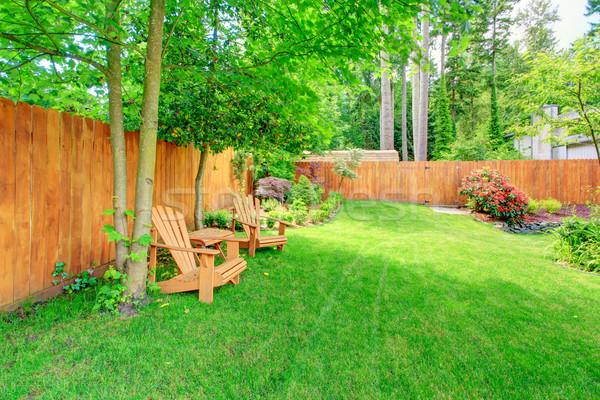 Fenced backyard with green lawn and sitting area Stock photo © iriana88w