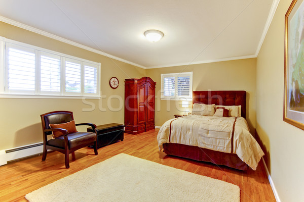 Cozy large guest room with suede brown bed and armor, hardwood floors and beige walls.  Stock photo © iriana88w
